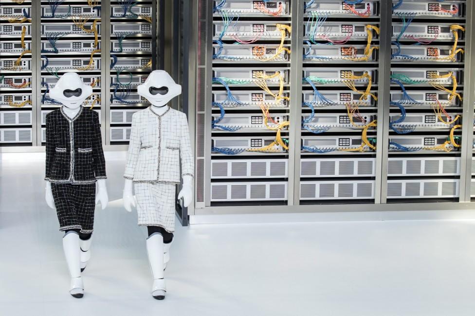 """- Екрани, електронно оборудване, бели стени и роботи, облечени в костюми тайори на """"Шанел"""". . . Творческият директор на модната къща Карл Лагерфелд..."""