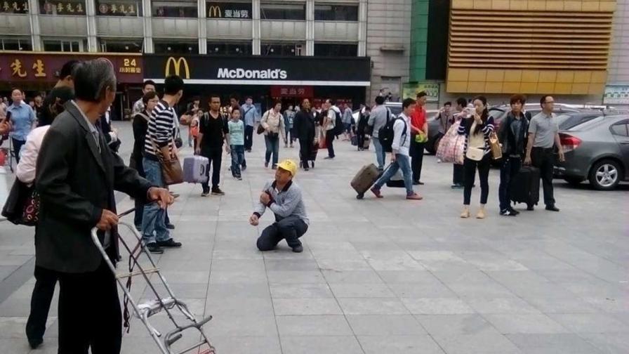 Мъж се превива от болка след като е ранен при нападението с нож на жп гарата в град Гуанчжоу