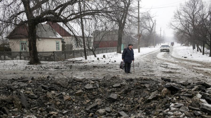 Мъж гледа кратера, образуван от снаряд на централната улица в село Дебатцево, в района на Донецк