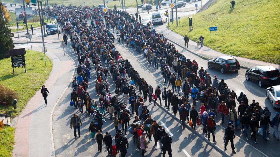 Словенски полицаи ескортират бежанци към границата с Австрия