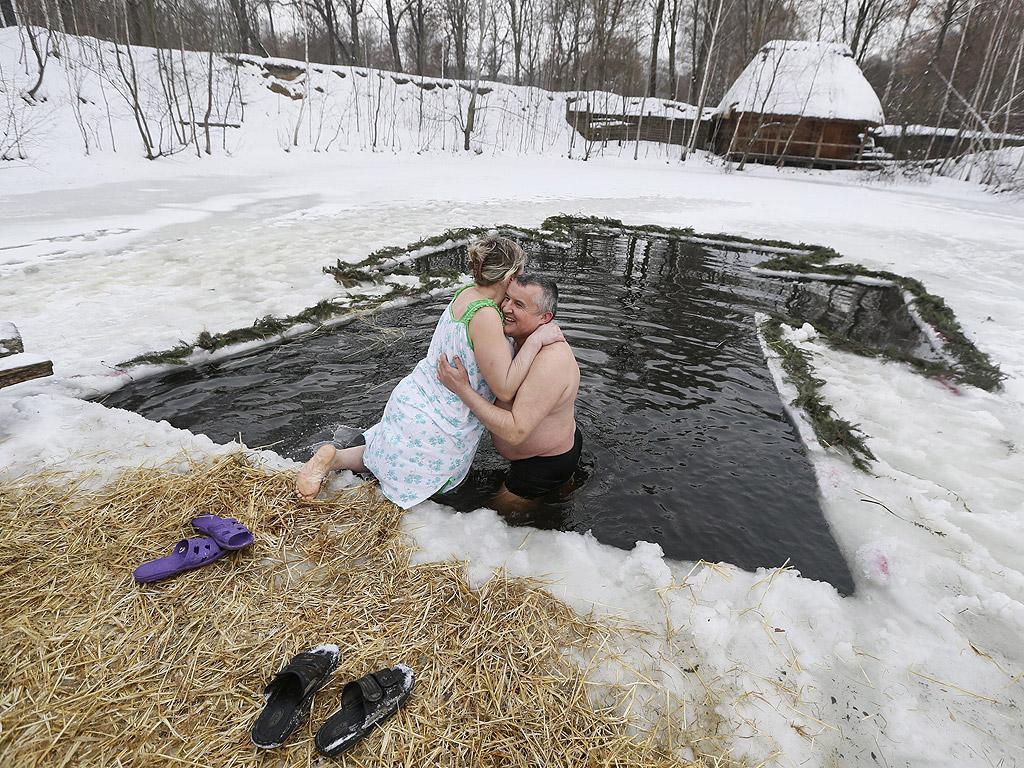 Православни вярващи се къпят в студена вода по време на Богоявленски тържества в Киев, Украйна. По време на Богоявление, някои хора вярват, че водите имат специални лечебни свойства и могат да бъдат използвани за лечение на различни заболявания, а много от тях правят ледени бани, като част от празника