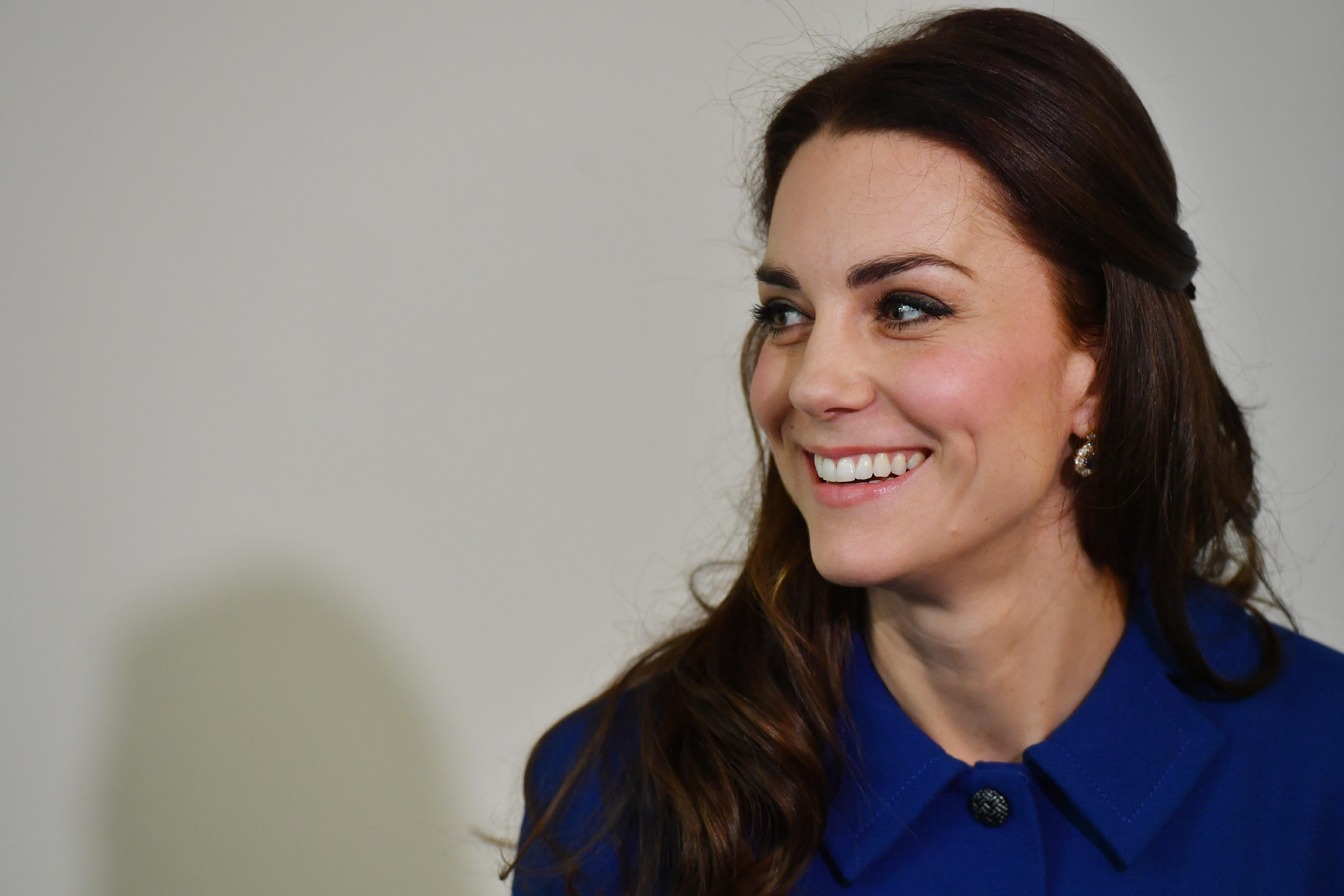 """За първото си официално събитие през 2017-а година Кейт Мидълтън се появи в елегантно палто тип рокля в кралско синьо, дело на български дизайнер. Дизайнът е на Петър Петров, който работи за английската марка """"Епонин"""". Фирмата е известна със стилните си дрехи в стилистиката на 50-те и 60-те години. Съпругата на принц Уилям избира за втори път техен тоалет."""