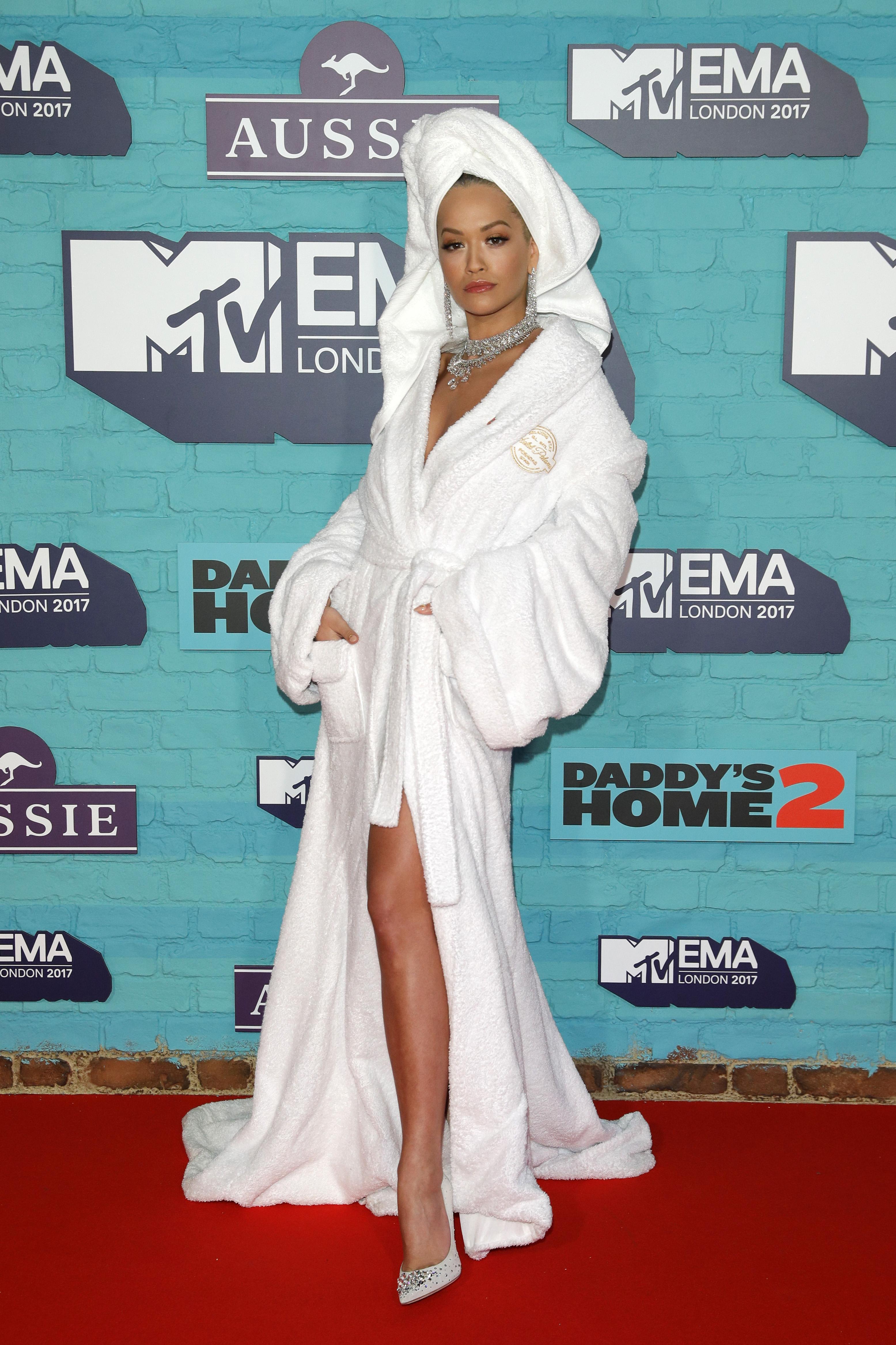 """Раздадоха се Европейските награди награди на MTV по време на пищнацеремония в зала """"Уембли"""", Лондон.Като на всички други награди, проведени от MTV, винаги има по няколко изненади.Тази година певицата Рита Ора, която бе водеща на наградите, """"събра погледите"""", преминавайки по червения килим в необичайно облекло- с хавлия и кърпа на главата.След шеговитата си поява в този вид, Ора сменяше тоалети буквалнопрез няколко минути, каквато е традицията всяка година. Водещият на наградите се преоблича най-малко 7 пъти, а дрехите винаги са меко казано ексцентрични."""