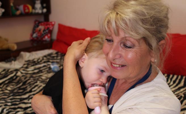 Патронажната сестра Нина Димова гушка едно от бебета на Галя  Елена. Източник: УНИЦЕФ България
