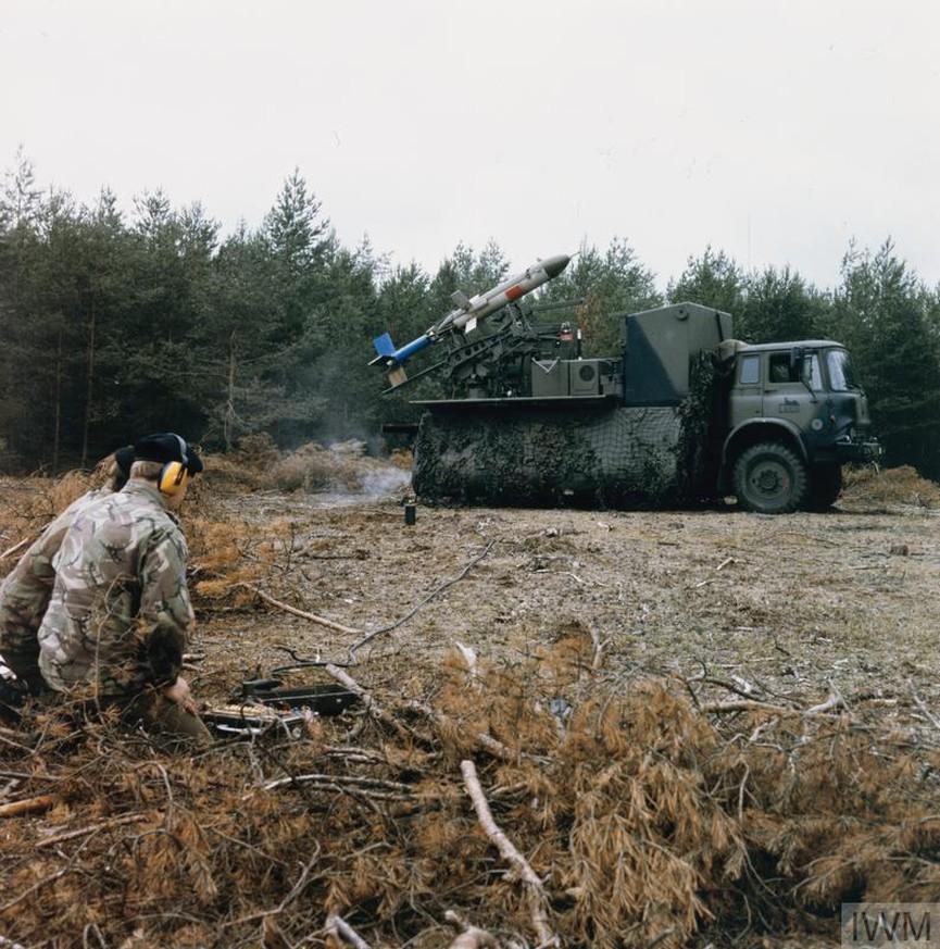 Двама войници се приготвят да пуснат дистанционно пилотирания дрон (RPV) по време на обучение в Германия, вероятно в началото на 80-те. Войниците управляват дрона чрез безжична клавиатура и джойстик.<br />