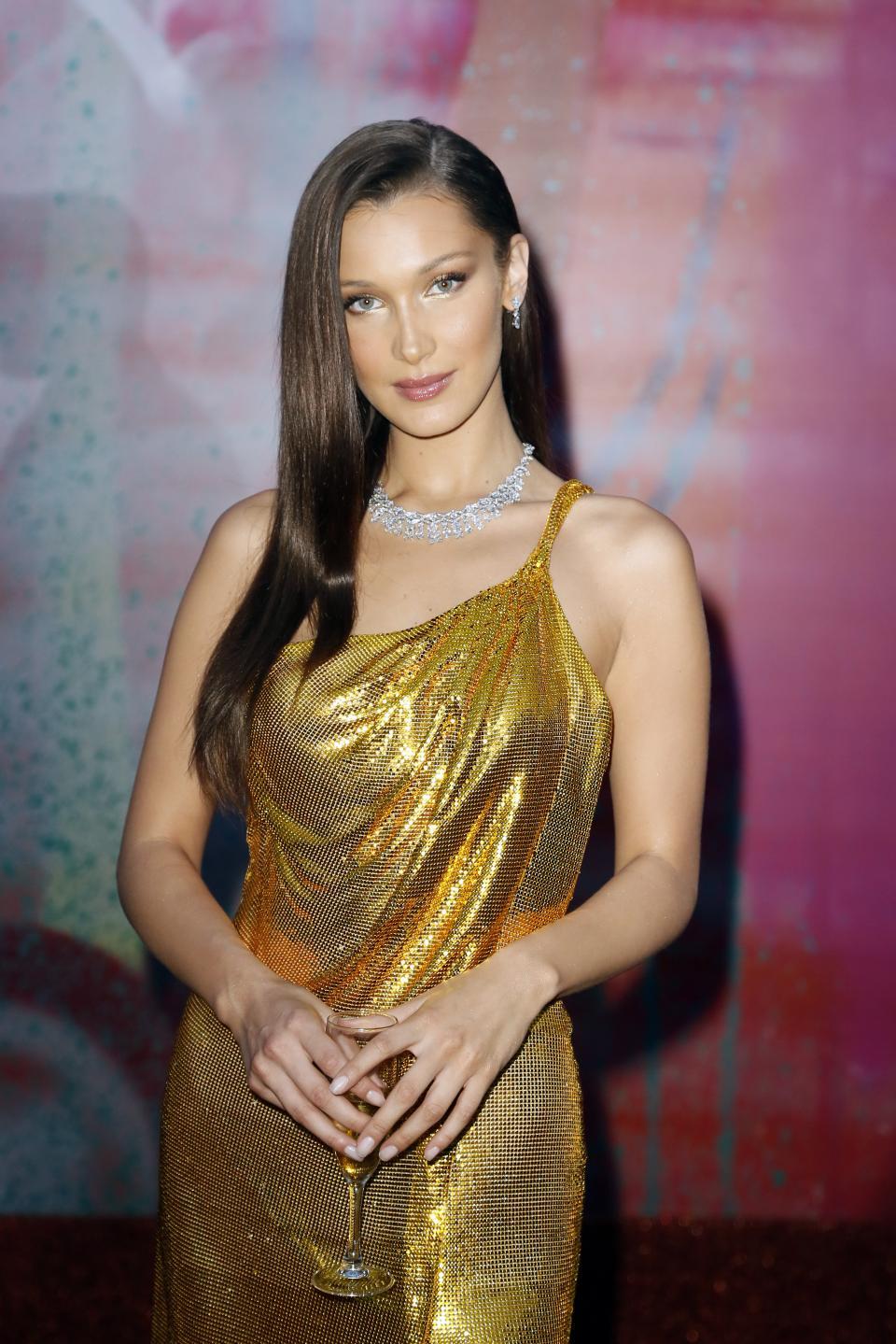 Световноизвестният моделБела Хадид за пореден път показа, че сияе като истинско бижуна червения килим. Красавицата бе сред гостите на светско събитие в Италия и привлече всички погледи с изумителна рокля със златисти отблясъци., Акцент в тоалета бе голямата цепка, която разкривашебезупречните крака на модела. Бела Хадид бе подбрала сребристи бижута като допълнение към роклята.