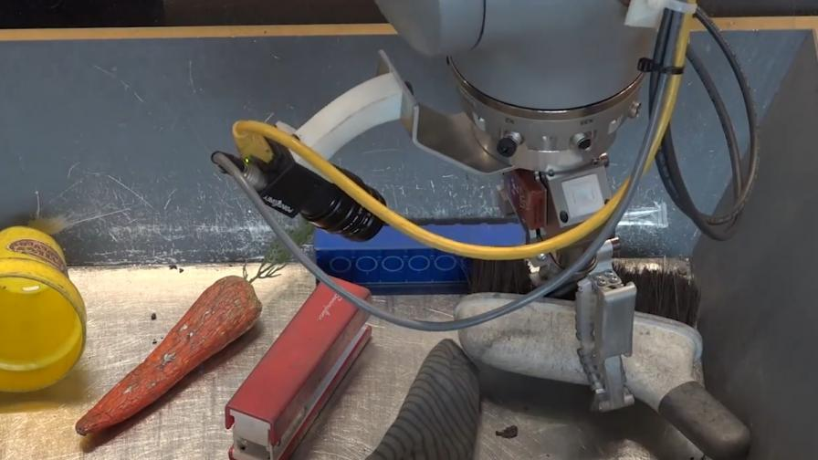 Роботът докосва предметите, за да разпознае четката и да я вземе