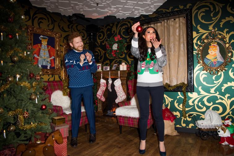 Блузата на Хари бесиня с принт на елени и снежинки, а пуловерът на много бременната Меган бес елф и снежинки.