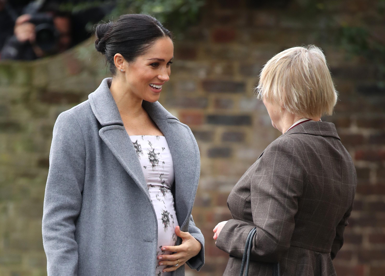 """Херцогинята на Съсекс Меган Маркъл се пошегува, че се чувствала """"много бременна"""" по време на първия си официален самостоятелен ангажимент при посещение на дом за социални грижи в Лондон."""