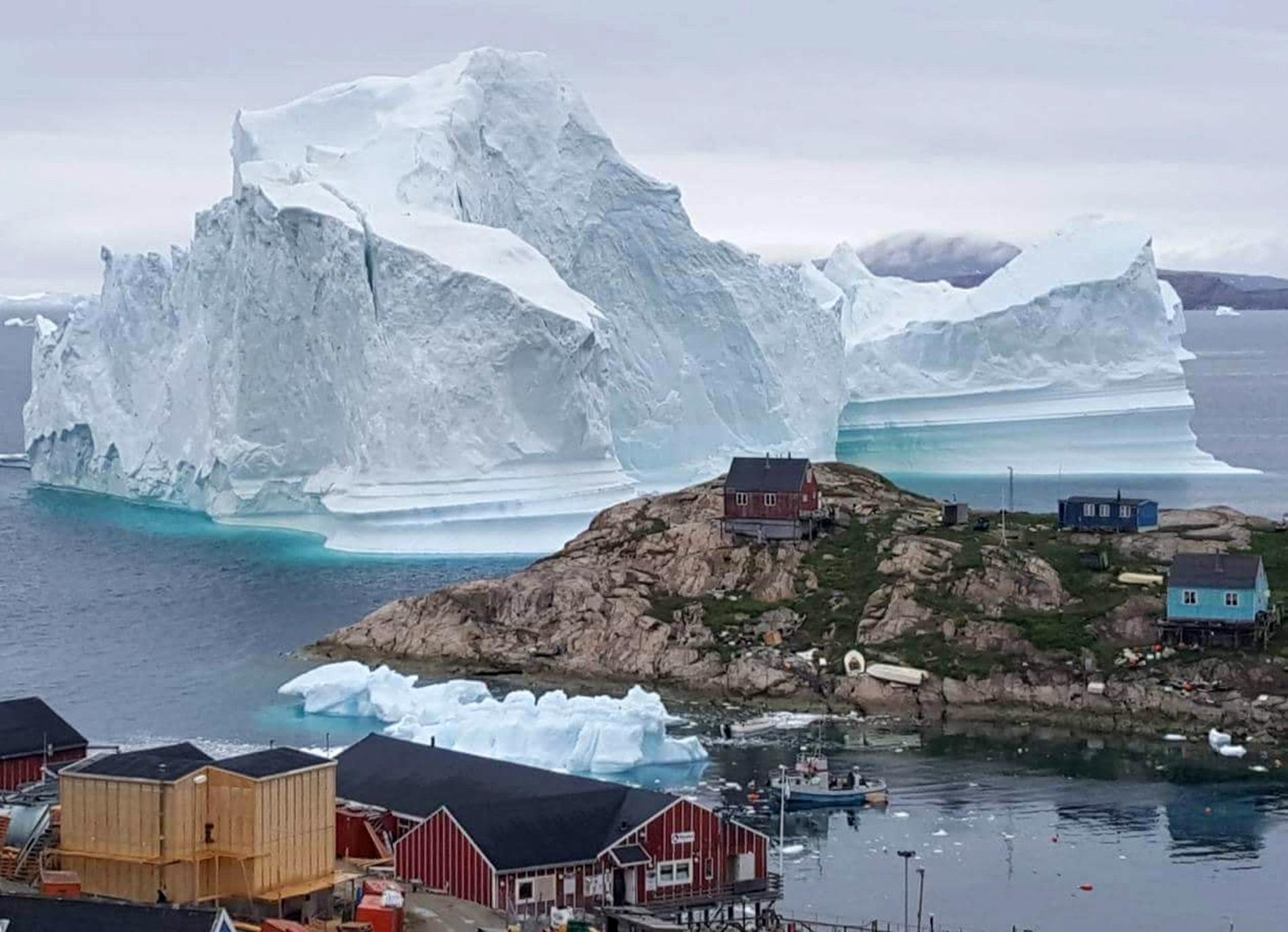 Айсберг притесни малкото селце Иннаарсуит, в Северозападна Гренландия, 12 юли 2018 г. Заради огромният леден къс с размери около 6 километра над 100 метра височина част от селото бе евакуирано.