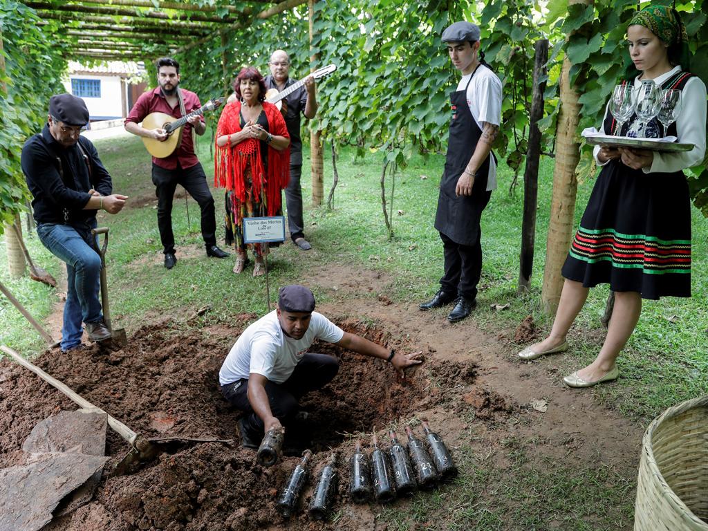 """Ритуалът за разкопаване на """"виното на мъртвите"""", е необичаен празник, за бразилския винопроизводител Оливардо Саки, верен последовател на традицията, родена в старата португалска империя."""