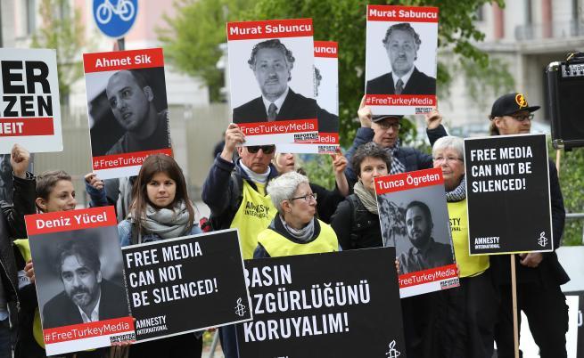 На снимката: Активисти на протест пред Турското посолство в Берлин, държейки снимки на журналисти, арестувани в Турция. 3 май, 2017 г.
