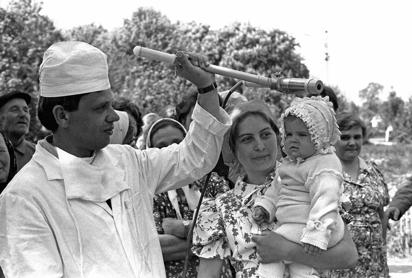 9 май 1986 г.: Съветски техник проверява бебе (Катя Литвинова) за радиокативно облъчване в село в близост да Киев.