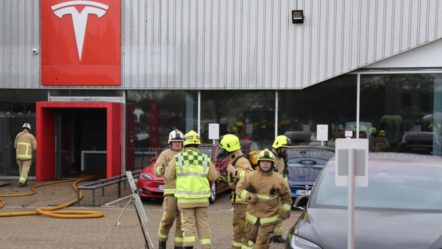 Пожарникари потушават пламналото дилърство на Tesla в Краули, Западен Съсекс, Англия.