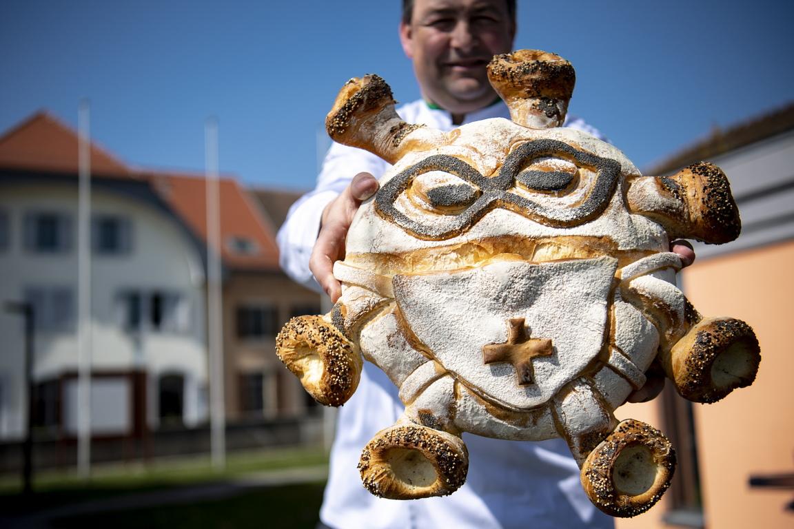 <p>Хлебарят Паскал Клемент показва хляб, изобразяващ смесица от коронавирус и медицинска сестра, носещи защитна маска за лице в хлебопекарната си в Daillens, Швейцария.</p>