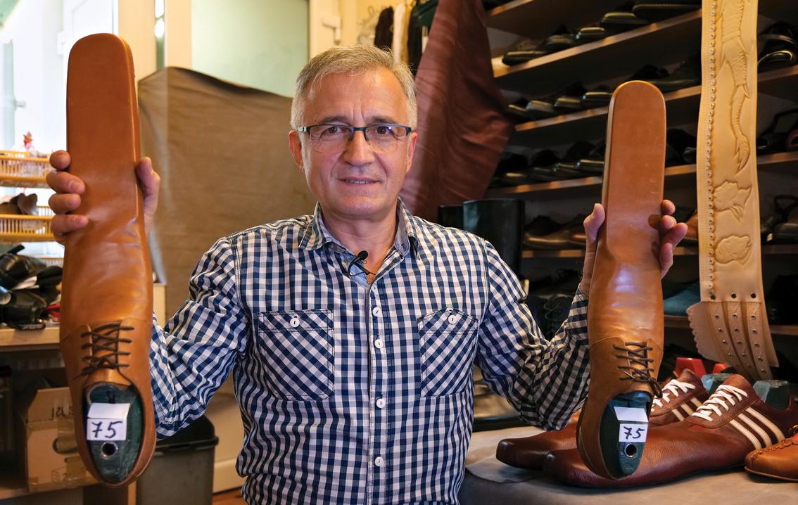 <p>Румънският обущар Григоре Луп показва чифт мъжки обувки за социално дистанциране, които е изобретил по време на пандемията на Коронавирус, в своята работилница в град Клуж Напока, на 500 км северозападно от Букурещ, Румъния</p>