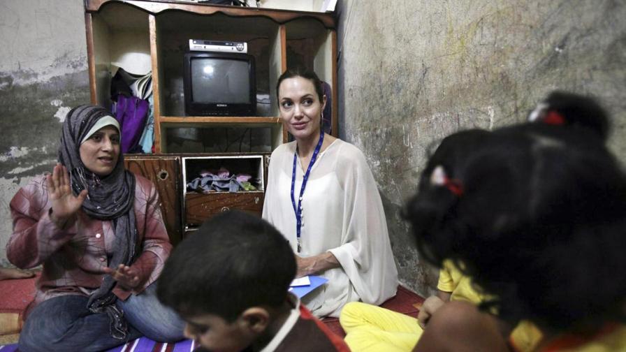 Анджелина с иракчанка и семейството й в бежански лагер в Дамаск през 2009 г.