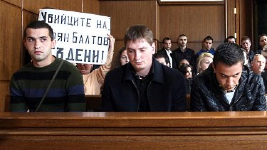"""В залата, зад тримата подсъдими, бе издигнат плакат: """"Убийците на Стоян Балтов - осъдени!"""""""