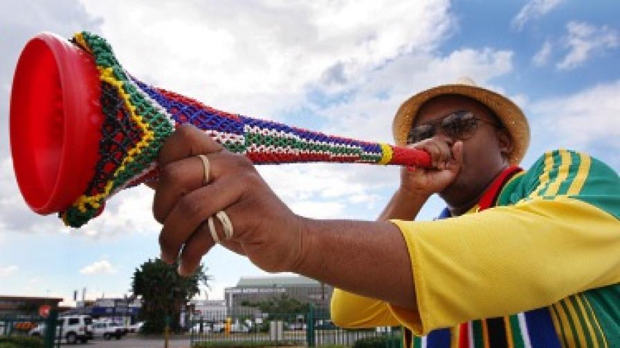 Местен запалянко в цветовете на националния футболен тим надува пластмасовата вувузела