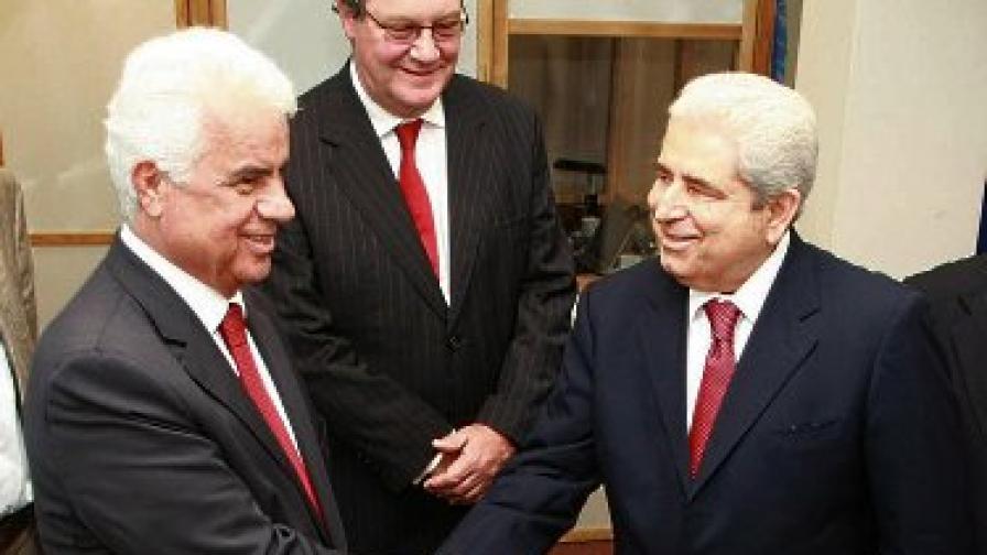 Дервиш Ероглу (вляво) и Димитрис Христофиас се ръкуват по време на среща в Никозия през май