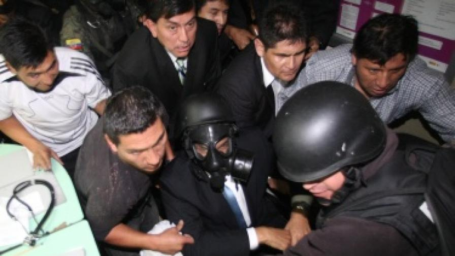 Президентът Рафаел Кореа (в инвалидната количка, с противогаз) бе изведен от болничната стая, където бе блокиран