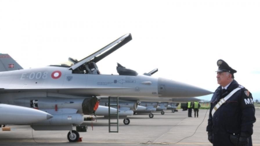 Италиански карабинери охраняват участващи в операцията самолети F16 на датските ВВС на военно летище на остров Сицилия
