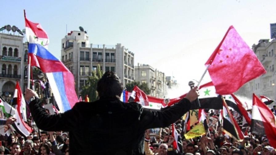 Проправителствени демонстранти развяват руското и китайското знаме, както и портрети на президента Башар ал Асад, на митинг в подкрепа на режима в Дамаск, ден след ветото в Съвета за сигурност на ООН