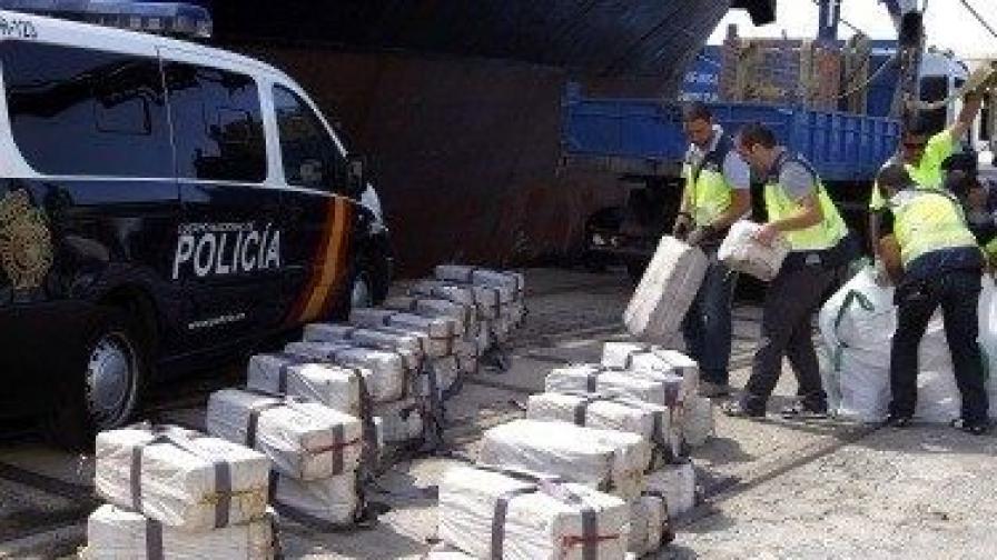 Испански полицаи разтоварват кокаина, заловен на българския кораб
