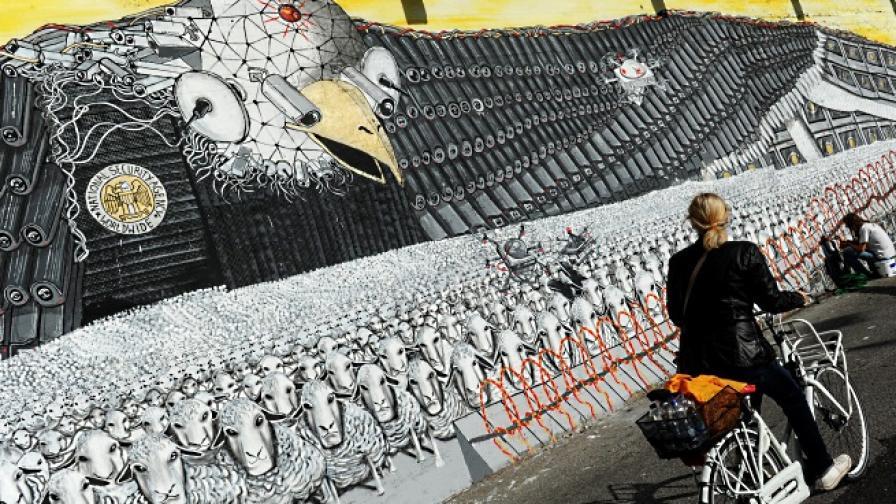 Колоездачка минава покрай стена в германския град Кьолн, на която е изобразен американският белоглав орел (символ на САЩ), който шпионира овце